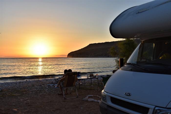 Sosta libera con il camper a bordo spiaggia durante un magnifico tramondo